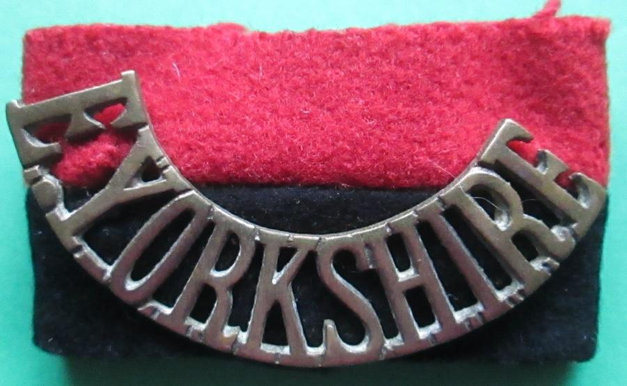 A RARE WWII EAST YORKSHIRE SHOULDER TITLE AND REGIMENTAL BACKING