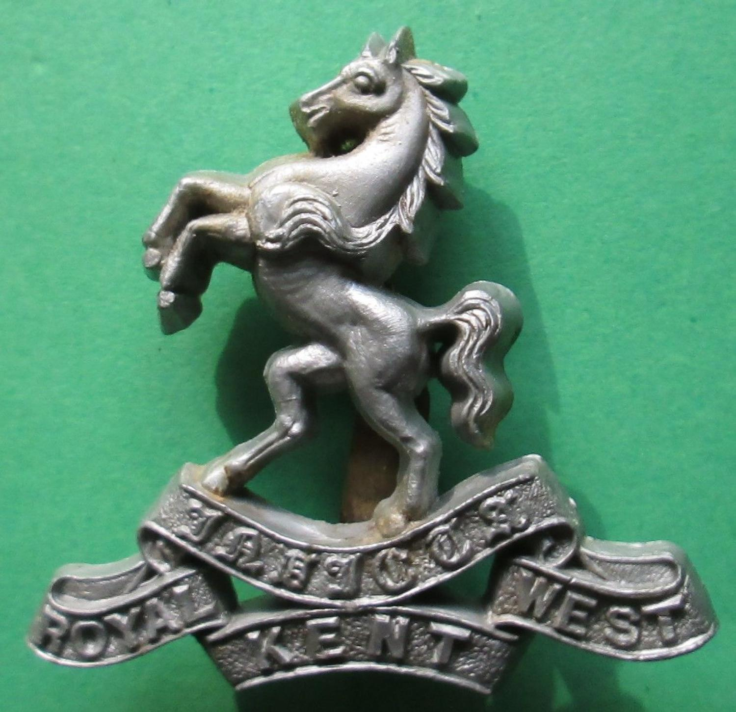 A PLASTIC WWII ROYAL WEST KENT CAP BADGE