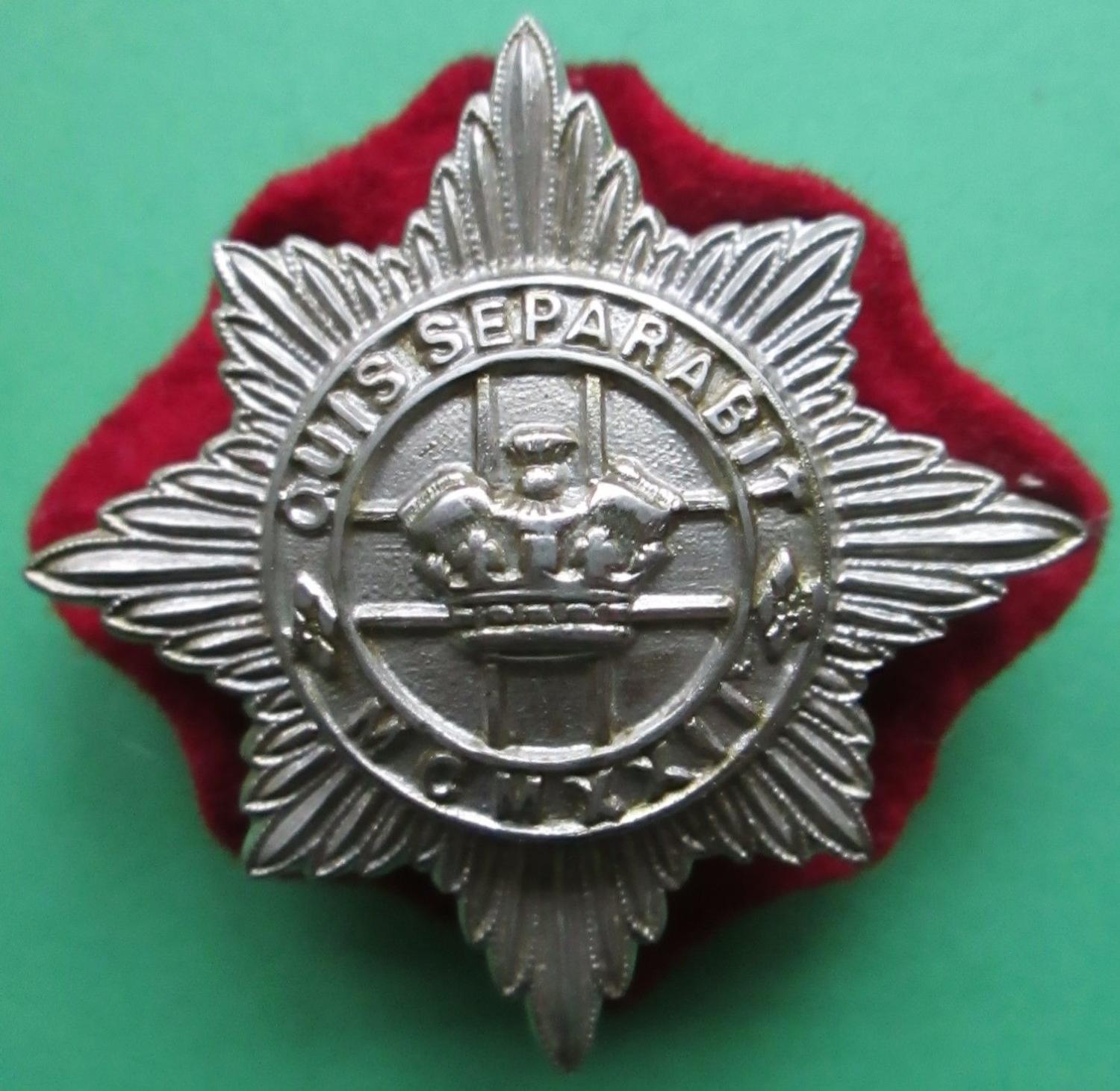 A 4TH / 7TH HUSSARS OTHER RANKS CAP BADGE WITH ITS RED BACKING CLOTH