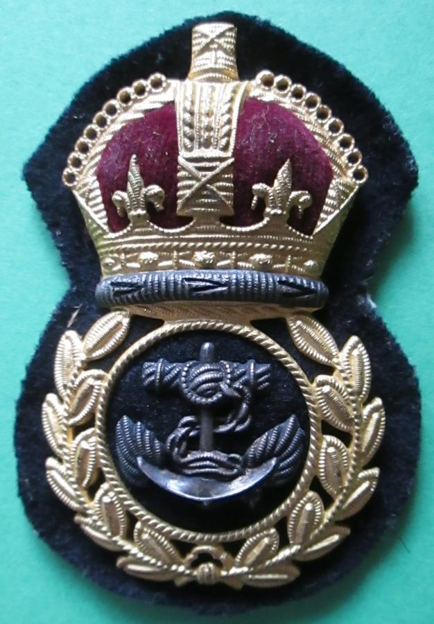 A WWII ECONOMY CHIEF PETTY OFFICERS GILT AND SILVER CAP BADGE