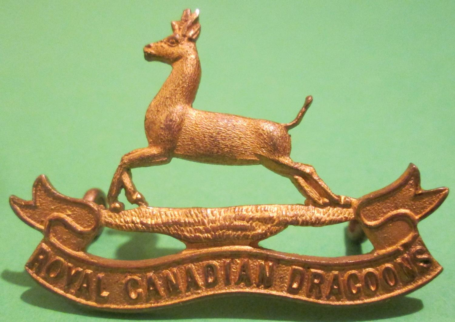 A ROYAL CANADIAN DRAGOONS GILT CAP BADGE
