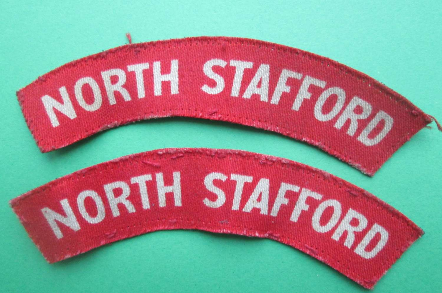 A GOOD USED PAIR OF NORTH STAFFORDSHIRE REGT SHOULDER TITLES