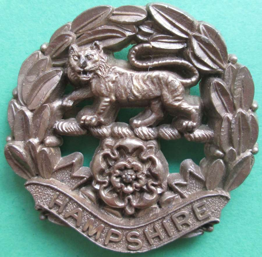 A PLASTIC HAMPSHIRE REGIMENT CAP BADGE
