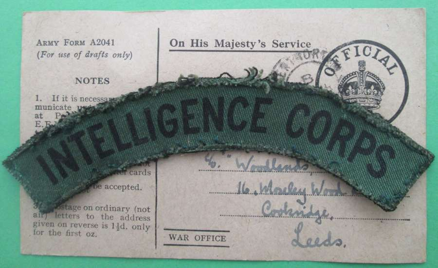 AN INTELLIGENCE CORPS SHOULDER TITLE WITH CORRESPONDING POSTCARD