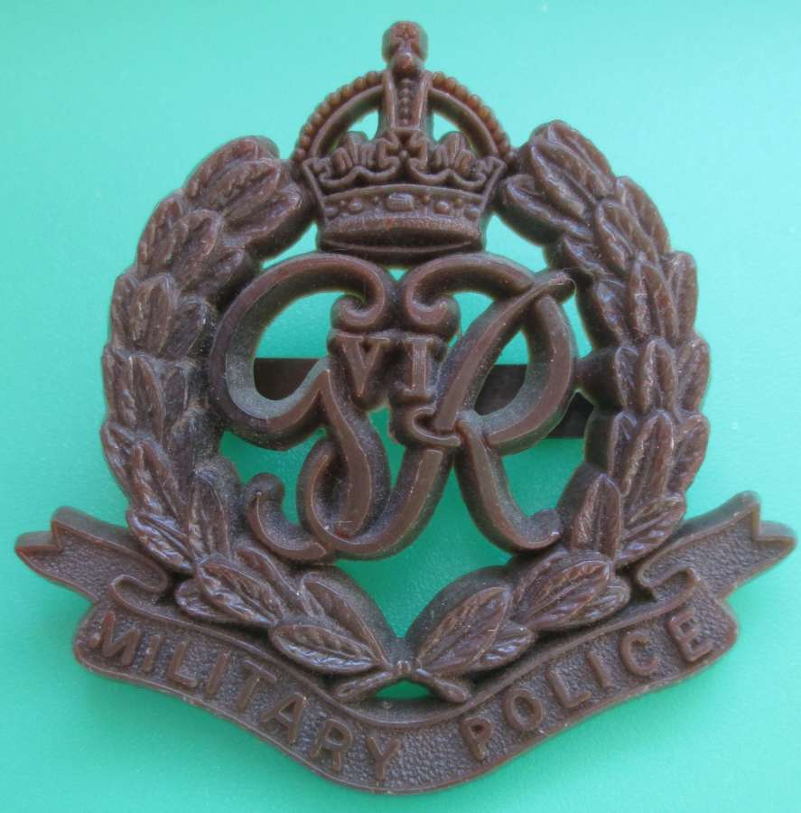A PLASTIC MILITARY POLICE BADGE