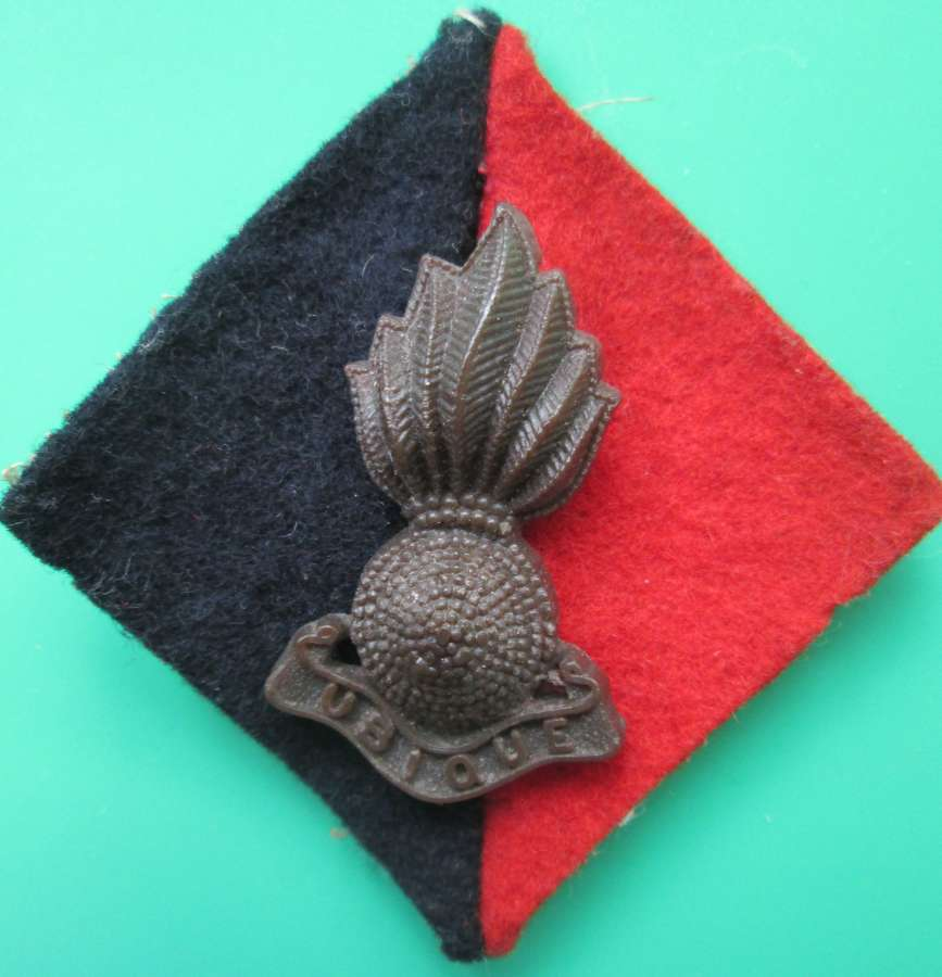 A ROYAL ARTILLARY CAP BADGE ON FLASH