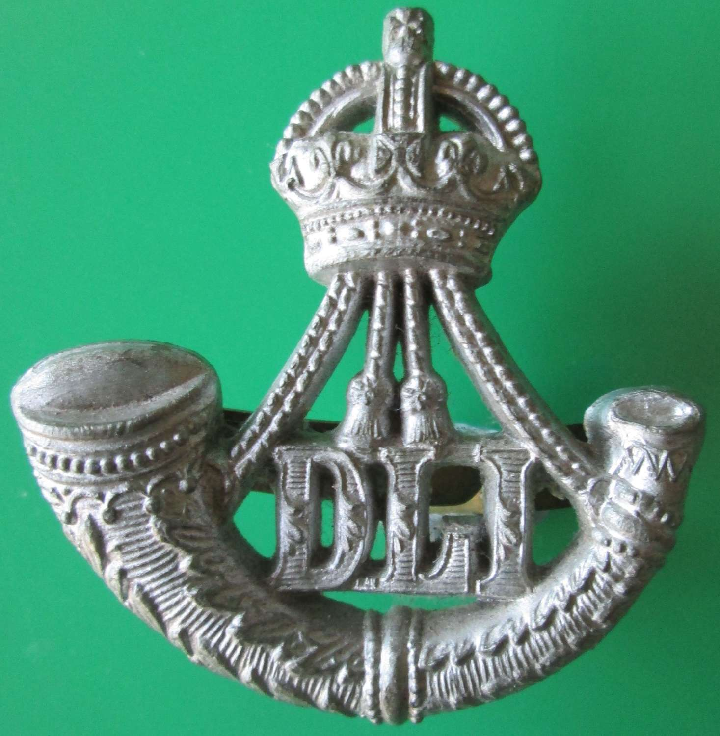 A WWI PLASTIC DURHAM LIGHT INFANTRY CAP BADGE