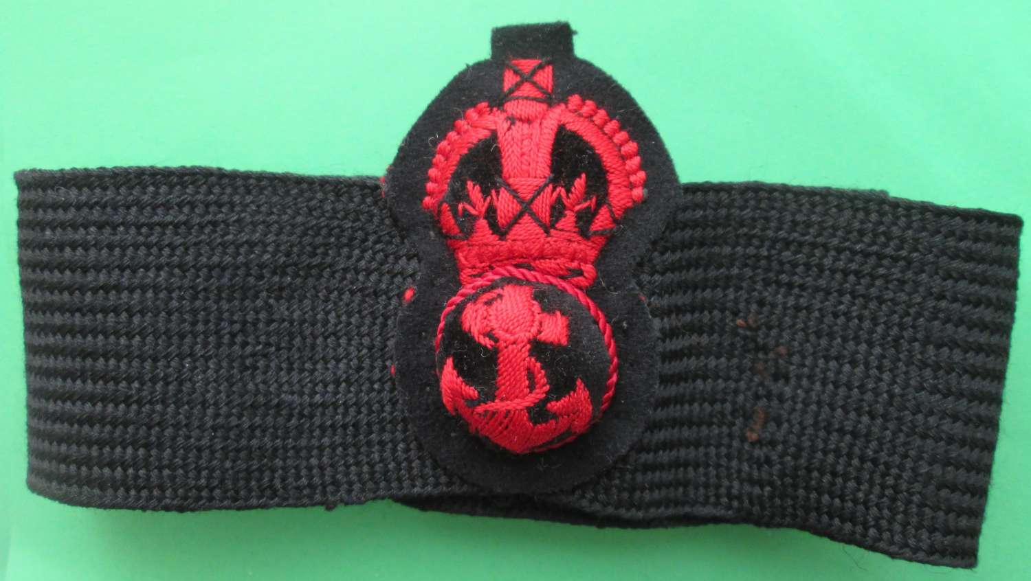 A PRE 1952 PETTY OFFICER'S CAP BADGE AND BAND
