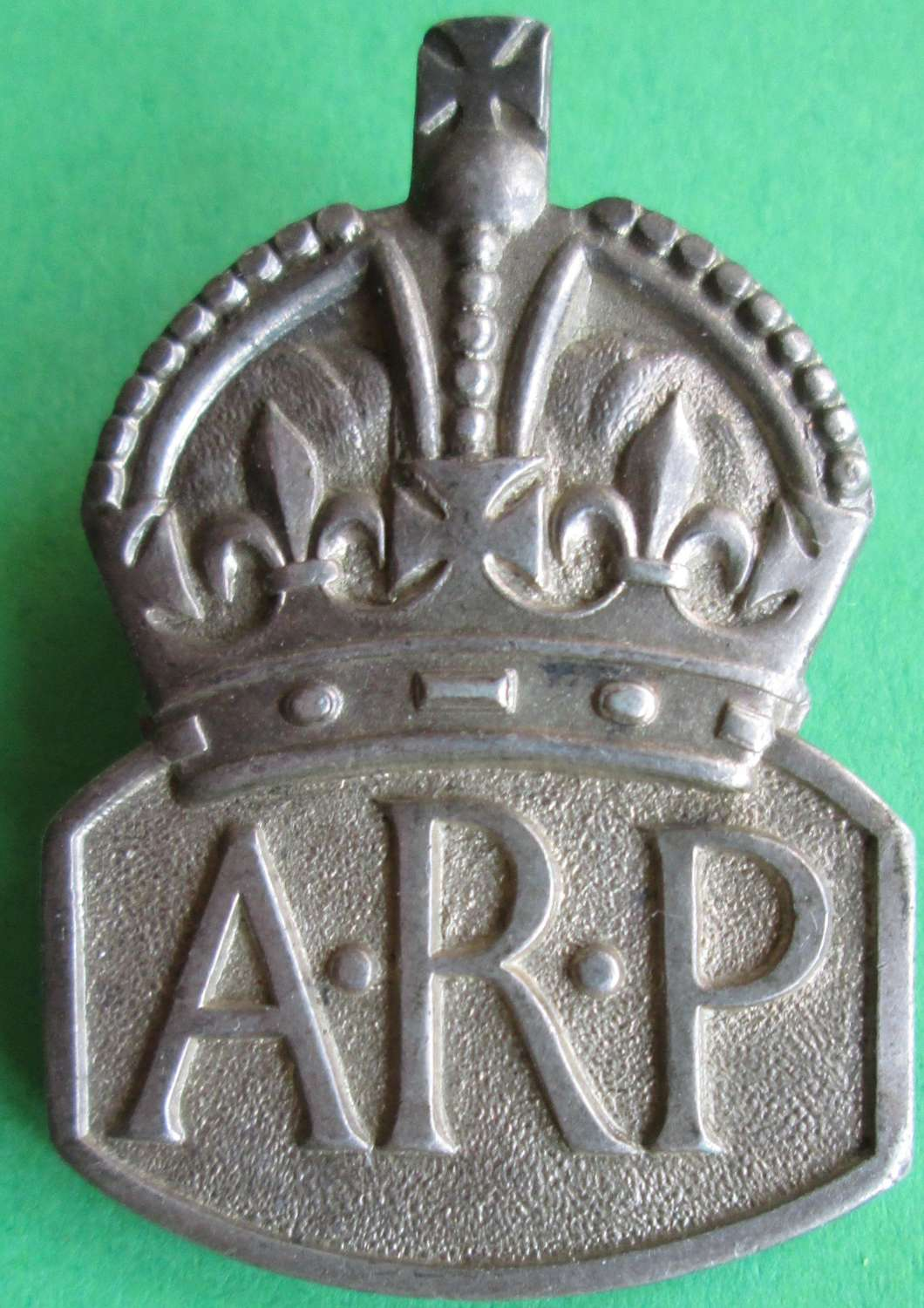 A SILVER ARP LAPEL BADGE
