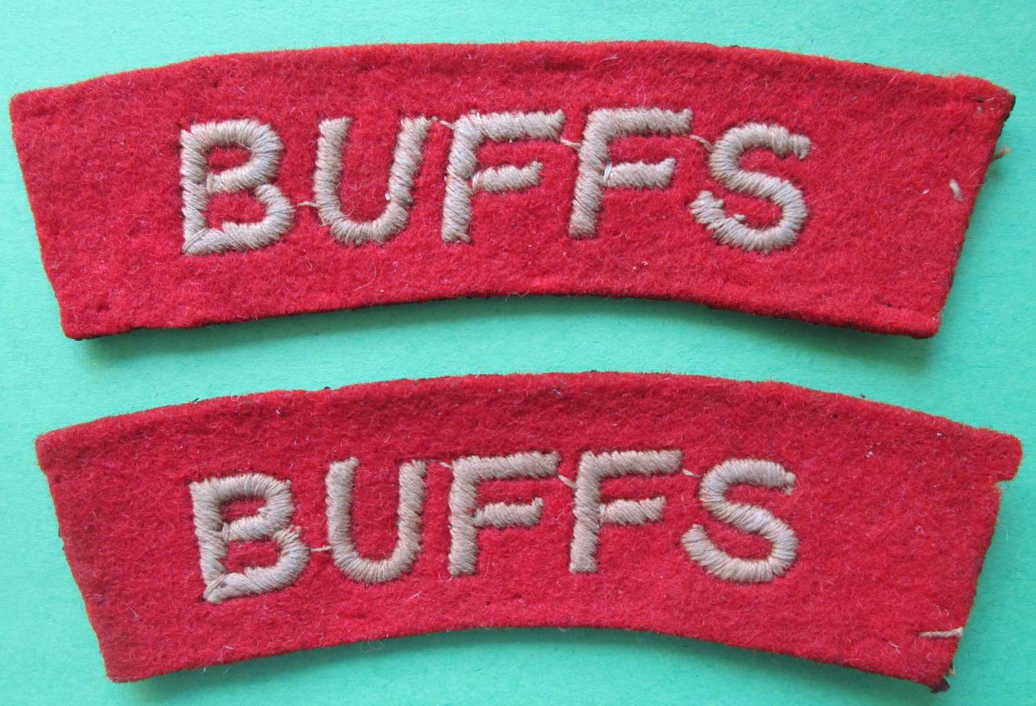 A PAIR OF BUFFS WWII SHOULDER TITLES